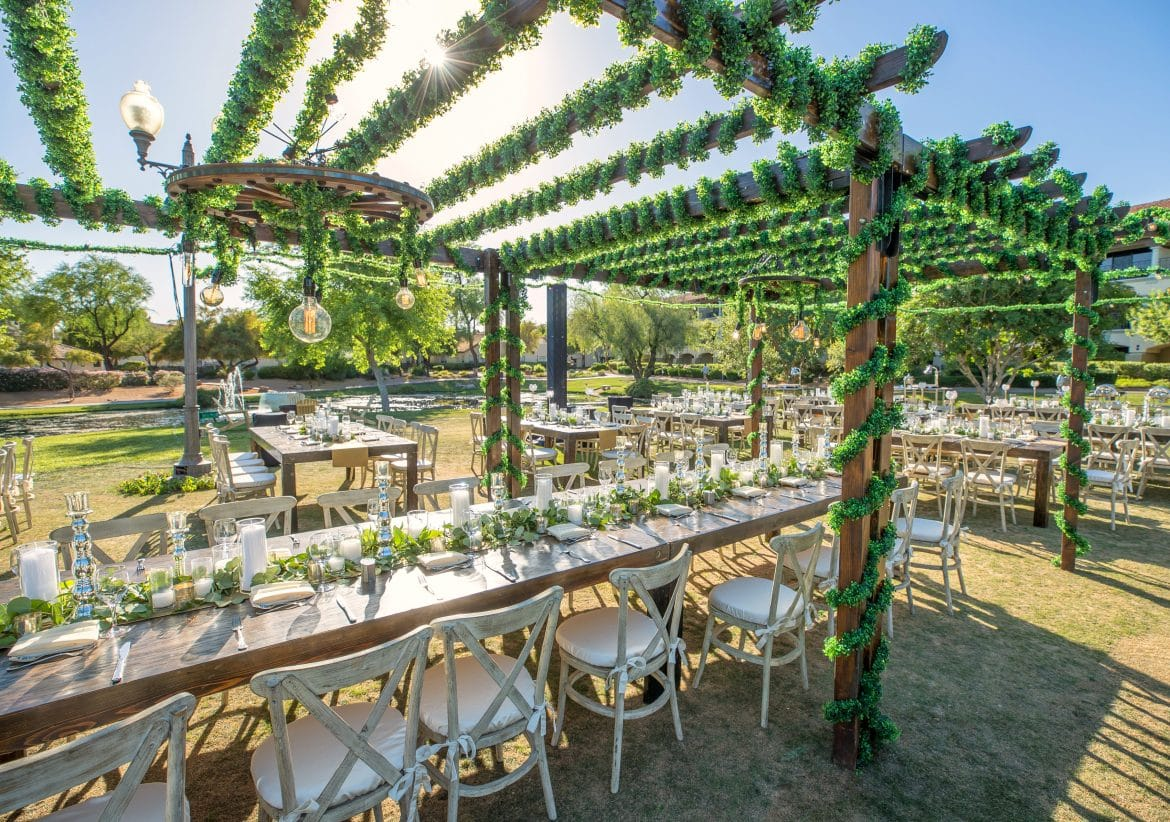 Outdoor desert garden event for upscale corporate dining event with vine wrapped trellis, industrial lighting and white and wood tables and chairs.