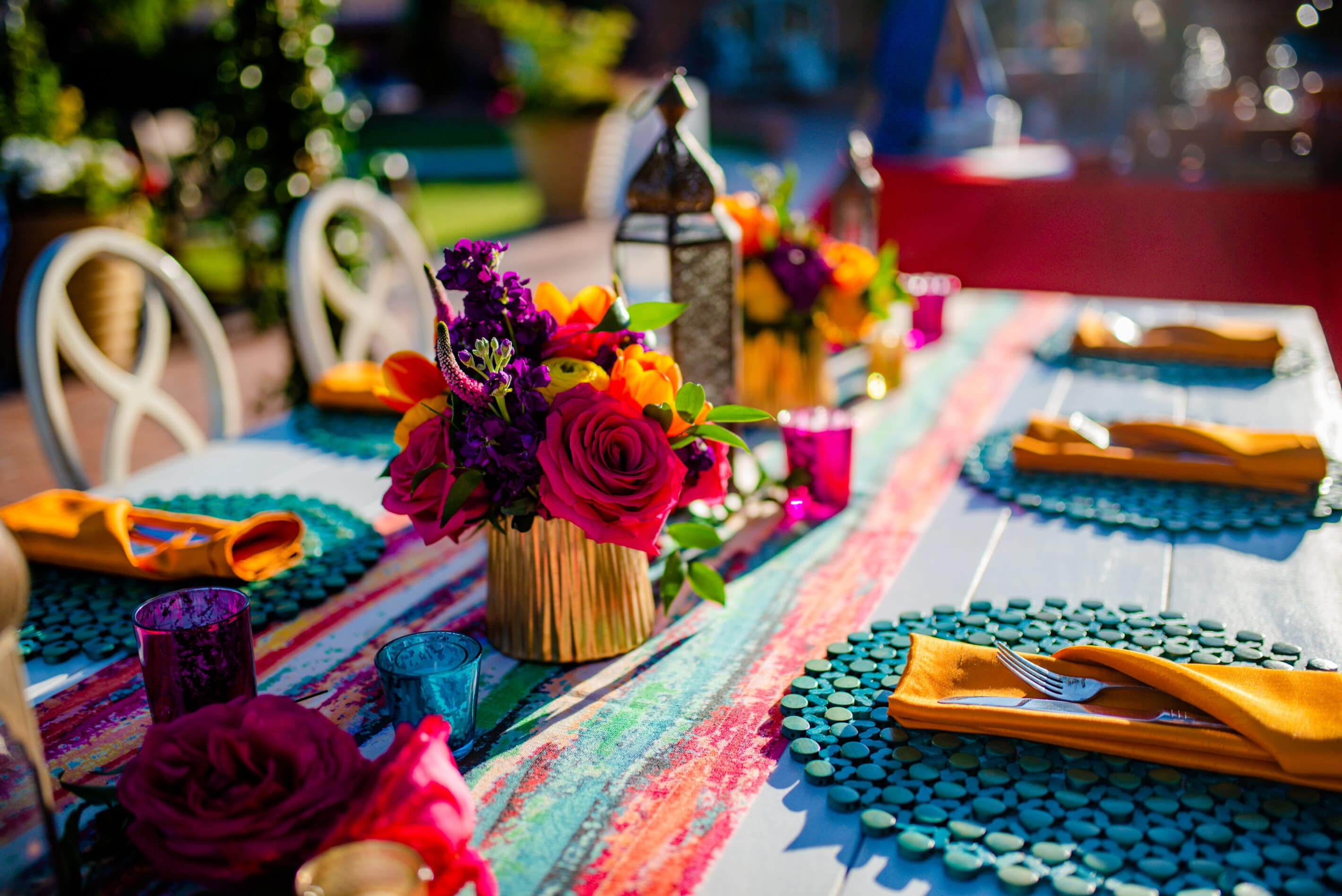 Bright florals in gold vases, serape like upscale runners, southwestern accents and other Mexican influenced decor items create a beautiful Upscale Fiesta corporate dinner event.