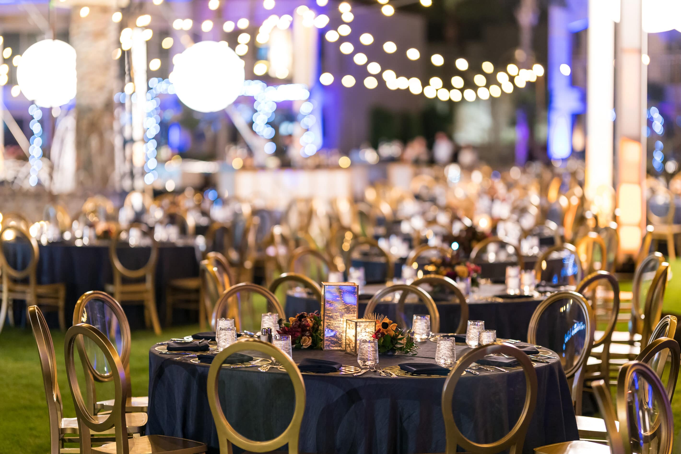 Elegant corporate dining dinner event for indoor or outdoor space at a Scottsdale resort or venue. Dining under the stars with blue and gold tones, bistro lighting and candle light.